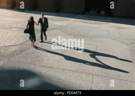 Businesswoman and a businessman walking forward to shake hands on a street with their long shadows on the ground. Business people greeting each other  - Stock Photo