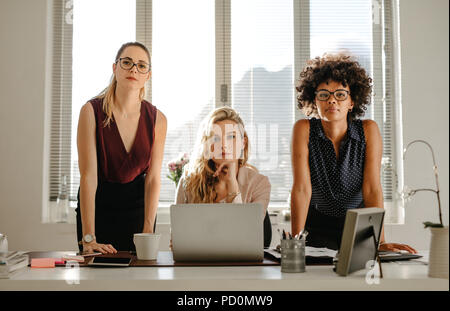 Portrait of three confident young businesswomen in casuals standing at office desk and staring at camera. Group of multi-ethnic businesswomen at start - Stock Photo