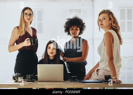 Group of multiracial businesswomen in casuals together at office desk and looking at camera. Female startup business team portrait. - Stock Photo