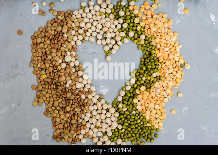 Variety of grains beans - mung, dry peas, lentils and chickpeas in jars on grey concrete background - Stock Photo
