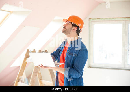 Shot of young engineer holding laptop in his hand while standing at construction site and working. - Stock Photo