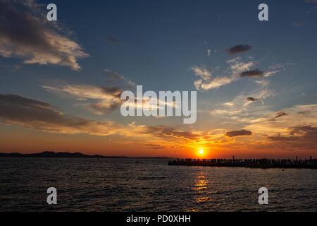 Zadar, Croatia - July 23, 2018: People watching the sunset from a dock located in Zadar old town - Stock Photo