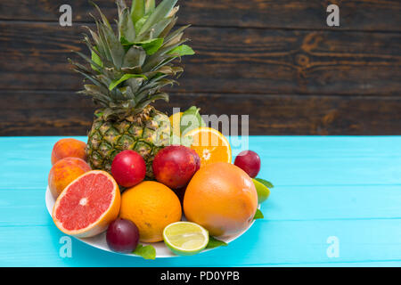 Plate of colorful healthy fresh tropical fruit with assorted citrus, nectarines, pineapple and plums on a turquoise blue table with copy space - Stock Photo