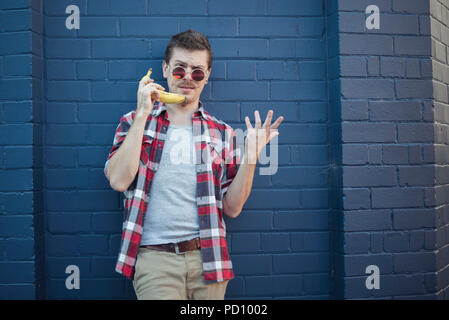 Young white man in hipster clothes, curly moustache, and vintage glasses, in front of a blue brick wall, using a banana as a phone. - Stock Photo