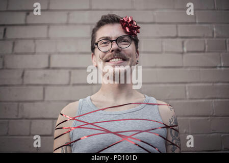 Young white man with tattoos wrapped in a red gift ribbon, with a red bow in the side of the head, curly moustache, and vintage glasses. - Stock Photo