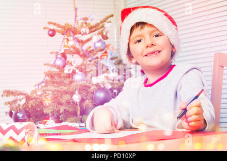 Smiling boy in Santa hat writing Christmas letter - Stock Photo