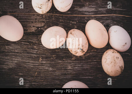 Dirty hen eggs on wooden table, top view - Stock Photo