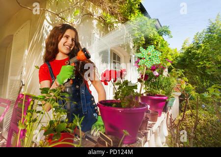 Happy girl watering plants on terrace garden - Stock Photo