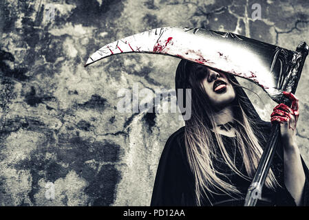 Demon witch licking blood on reaper. Female demon angel in black clothes and hood on grunge wall background. Halloween day and Mystery concept. Fantas - Stock Photo