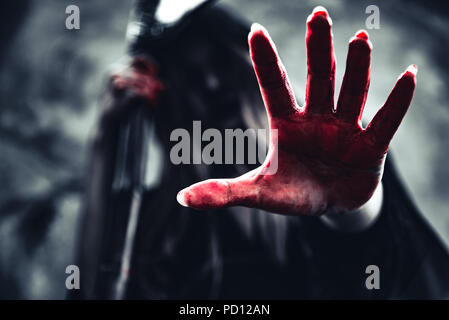 Witch showing bloody hand with reaper. Female demon angel in black clothes and hood on grunge wall background. Halloween day and Mystery concept. Fant - Stock Photo