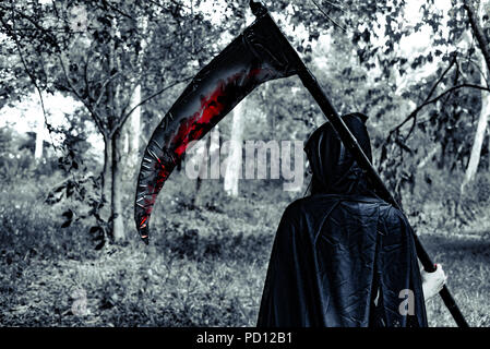 Back view of demon witch with reaper and blood in the mystery forest. Horror and Ghost concept. Halloween day and Scary scene theme. - Stock Photo