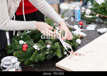 Woman tying a bow ribbon, decorated a Christmas wreath. Attaches toys and decor with glue gun. Hands close-up. Master class on making decorative ornaments. - Stock Photo