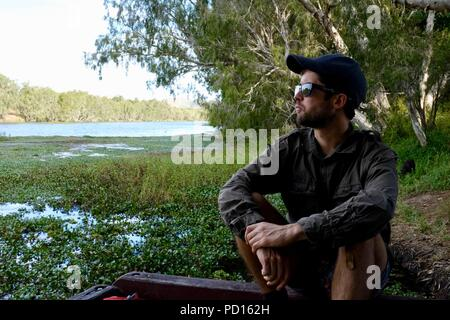 Man with sunglasses and a hat sitting on a jetty looking over the water, Booroona walking trail on the Ross River, Rasmussen QLD 4815, Australia - Stock Photo