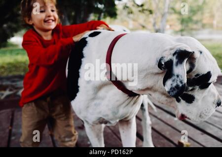 A young girl cuddles and smiles with a white and black great dane dog, Booroona walking trail on the Ross River, Rasmussen QLD 4815, Australia - Stock Photo