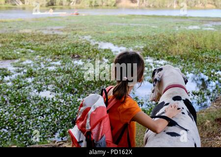 A young girl White and black great dane dog together overlooking a river, Booroona walking trail on the Ross River, Rasmussen QLD 4815, Australia - Stock Photo