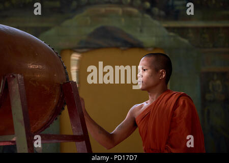 A young Buddhist monk playing a tambour during a ceremony at a monastery in Siem Reap, Cambodia. - Stock Photo