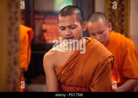 A young Buddhist monk chanting with his eyes closed during a ceremony in one of the temples within their monastery. - Stock Photo