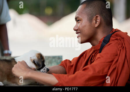 A smilling young Buddhist monk plays with a two-month old puppy in the monastery where he lives. In Siem Reap, Cambodia. - Stock Photo