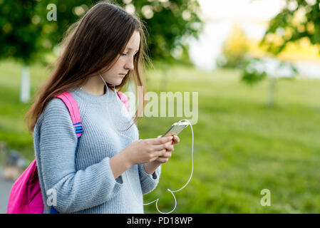 Girl schoolgirl student. In the summer on the street. In his hands holds a smartphone. Play music reads and writes messages on social networks. Free space for text. - Stock Photo