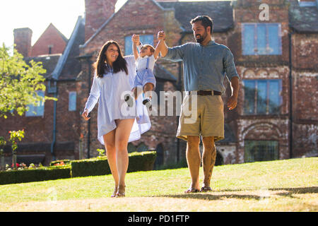 Birmingham, UK 5th August, 2018. Two-year-old Zachary Hickin enjoys some fresh air and the late afternoon sunshine with mum Charlie and dad Chris. The weather looks set to continue dry and warm for the coming week. Peter Lopeman/Alamy Live News - Stock Photo
