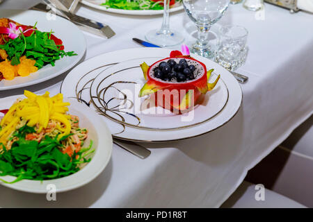 Red Dragon fruit juice in a dish straw, decorated with Plumeria flowers over flowery fabric. Top view. - Stock Photo