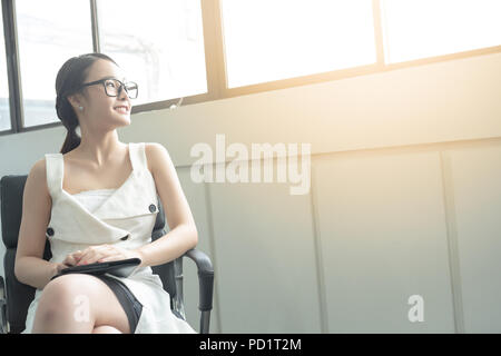 Young business woman in white dress who is candidate sitting wait for interview while looking out of big window. - Stock Photo
