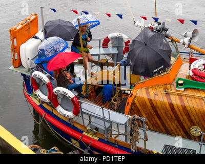 Passengers on the old Whitby Lifeboat 'Mary Ann Hepworth' in Whitby harbour waiting to go on a summer pleasure trip  umbrellas up in heavy rain - Stock Photo