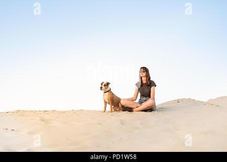 Beautiful young woman in sunglasses with dog sit on sand. Girl in hiking casual clothes and staffordshire terrier puppy sitting on sandy beach or in d - Stock Photo