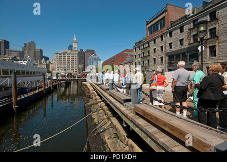 Tourists queue to boarding for a boat tour in the Boston Harbor, Suffolk County, Massachusetts, USA - Stock Photo