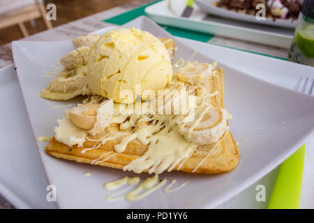 Belgian waffles with melted white chocolate, vanilla ice cream and coconut flakes on light wooden background. - Stock Photo