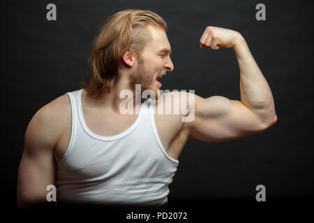 joyful athlete admiring with his strong arms isolated on the black background. happy result after workshop. look at the biceps - Stock Photo