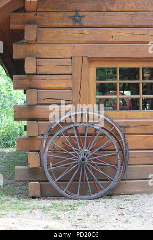 Two wooden wheels leaning against a log cabin at the Nature Center and interpretation station at the National Historic Landmark The Kennicott Grove in Glenview, Illinois on a bright sunny summer day. - Stock Photo