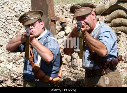 Torbay Steam Fair, Devon, England: Two First World War soldiers re-enact trench life as they aim rifles at the photographer - Stock Photo
