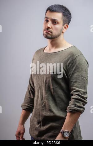 close up side view portrait of a handsome boy in grey sweatshirt.studio shot . fashion concept - Stock Photo