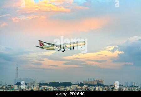 Airbus A330-200F Qatar Airways Cargo to fly over the clouds prepare landing Tan Son Nhat International Airport - Stock Photo