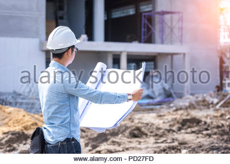 civil engineer working with blueprint for project quality control at construction site - Stock Photo