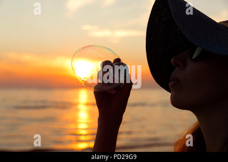 Woman portrait blowing soap bubbles at the beach. Beautiful sunset - Stock Photo