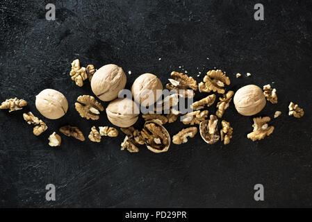 Organic Walnuts. Walnuts on black stone background, top view, copy space. - Stock Photo