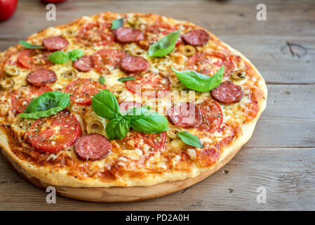 Italian Pizza with Tomatoes, Salami, green Olives, Cheese and Basil leaves on wooden table. Fresh Homemade Pizza, copy space. - Stock Photo