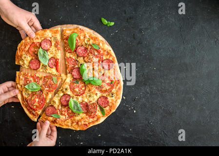 People Hands Taking Slices Of Italian Pizza. Italian Pizza and  Hands close up over black background, top view, copy space. - Stock Photo