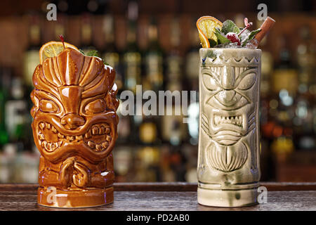 Set of two tropical cocktails - rum runner and ryo punch. Cocktails stand in a bar on a blurry background of alcohol. - Stock Photo