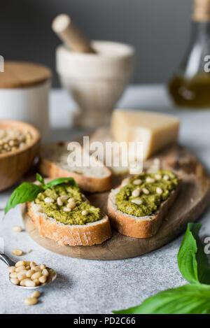 Italian pesto bruschetta on cutting board. Closeup view, selective focus - Stock Photo