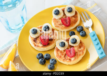 Fun food for kids. Pancakes with funny animal faces on colorful yellow plate. Kids meal. Selective focus - Stock Photo