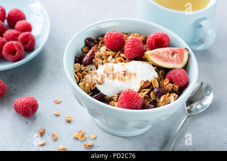 Granola with yogurt, berries and fruits in bowl. Healthy tasty breakfast with yogurt, homemade granola, fresh raspberries and figs. Cup of green tea o - Stock Photo