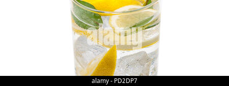 A full jug of drink from ice, lobules of fresh yellow lemon and crystal clear water. - Stock Photo