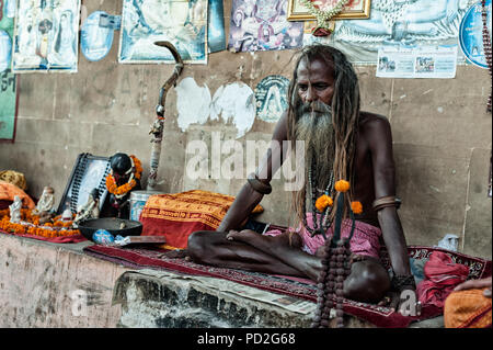 A hindu sadhu (holy man) on the Ganges River ghat of Varanasi, Uttar Pradesh, India - Stock Photo