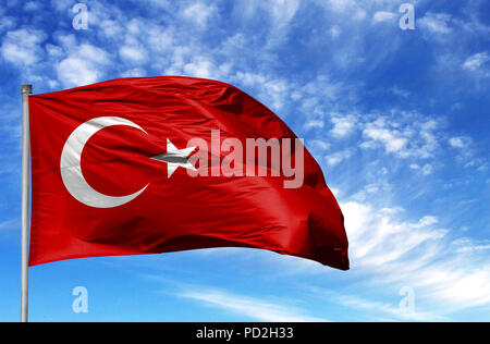 National flag of Turkey on a flagpole in front of blue sky. - Stock Photo