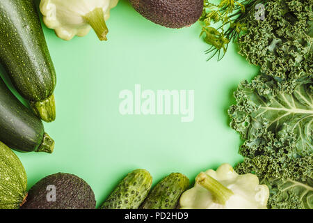 Assortment of green vegetables on green background, top view. Fruits and vegetables containing chlorophyll. - Stock Photo