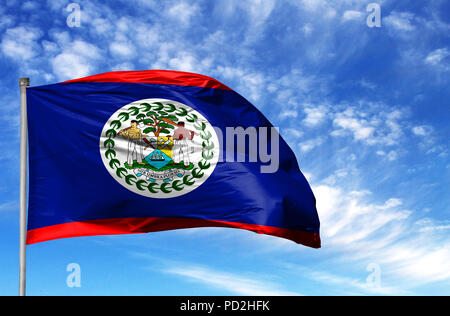 National flag of Belize on a flagpole in front of blue sky. - Stock Photo