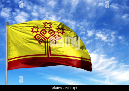National flag of Chuvashia on a flagpole in front of blue sky. - Stock Photo